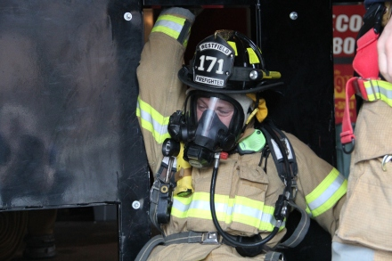 Firefighter Scott Wolfe maneuvers through a tight wall space during training this week.