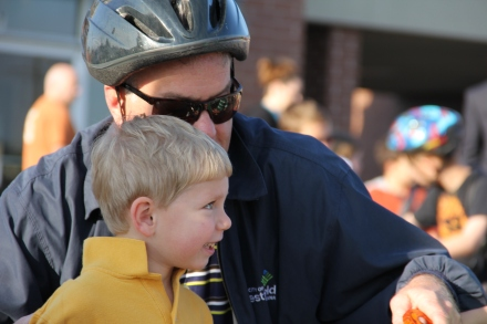Mayor Andy Cook helps a young boy prepare for today's exciting bike ride to school.