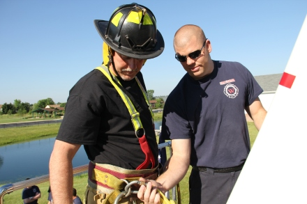 Firefighter Josh Southerland tethers a safety line to Steve Ward before his  123-foot ladder climb.