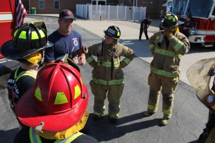 Lieutenant Matt Mills explains how to operate a firehose to firefighter-for-a-day candidates.