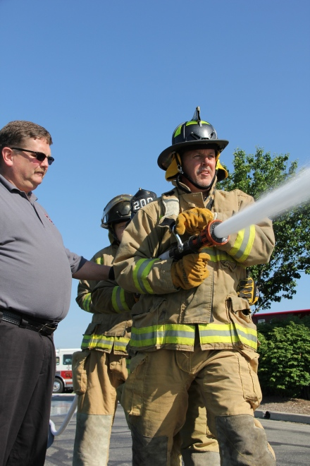 Division Chief Garry Harling helps Steve Ward of IMMI and Amber Willis of CSI Signs spray water on a pretend fire.